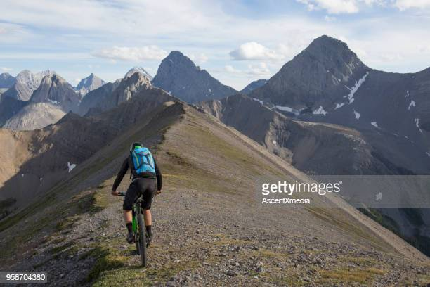 mountain biker traverses high mountain ridge crest - kananaskis country stock pictures, royalty-free photos & images