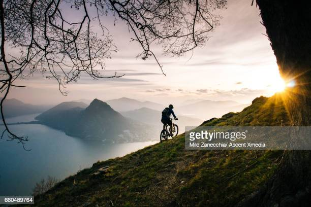 Mountain biker traverses steep mountain slope above lake