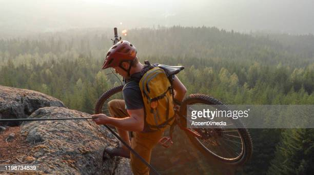 mountain biker uses rope for ascent, above mountains and valley - ascent xmedia stock pictures, royalty-free photos & images