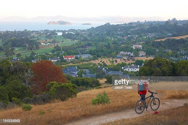 mountain biker walking bicycle along bay view. - san rafael california stock pictures, royalty-free photos & images