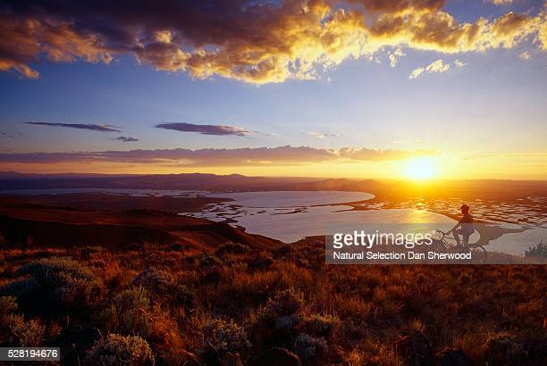 mountain biker watching sunset at warner potholes - dan sherwood photography stock pictures, royalty-free photos & images