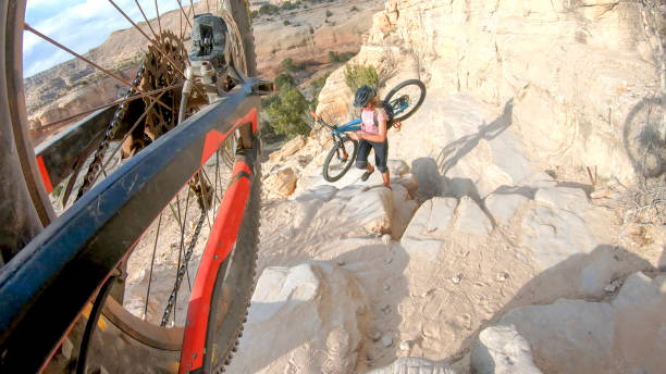 POV of mountain bikers ascending a steep canyon