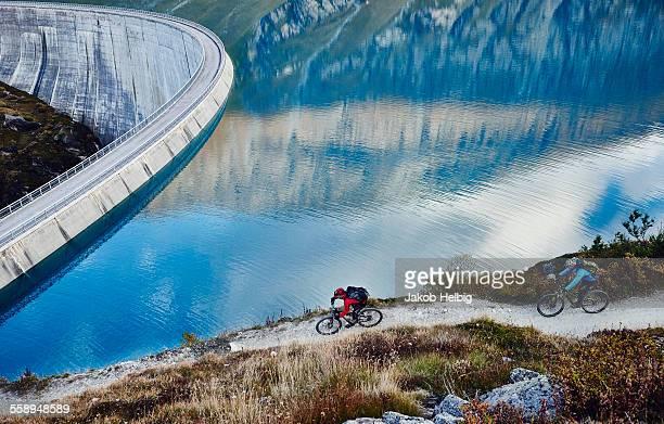 mountain bikers by reservoir, valais, switzerland - reservatório - fotografias e filmes do acervo