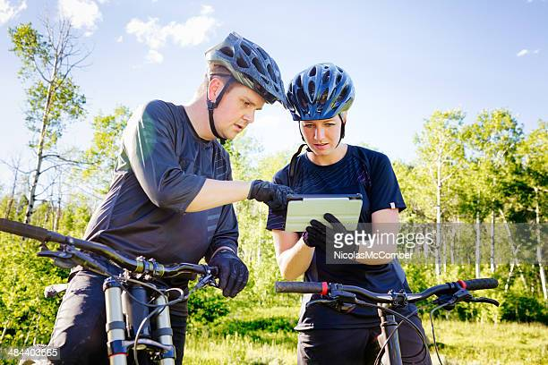 Mountain bikers checking map on digital tablet