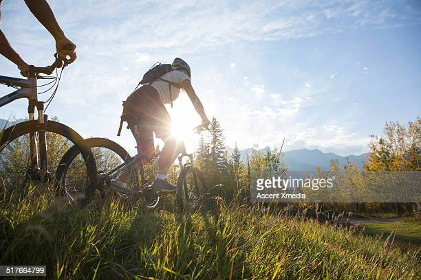 Mountain bikers descend mtn ridge crest, autumn