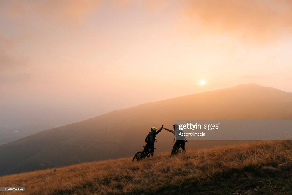 Os motociclistas da montanha dão elevado-cinco no por do sol : Foto de stock