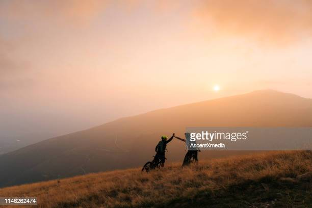 mountain bikers give high-five at sunset - mountain biking stock pictures, royalty-free photos & images