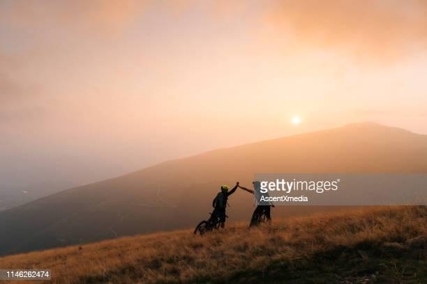 mountainbiker geben high-fünf bei sonnenuntergang - erforschung stock-fotos und bilder