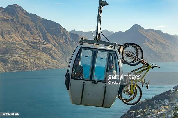 Mountain Bikers in Skyline Gondola Going Over Queenstown City