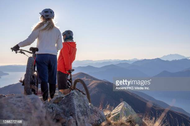 mountain bikers pause on the top of a mountain and look out - look back at early colour photography imagens e fotografias de stock