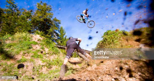 Mountain bikers performing stunts against sky