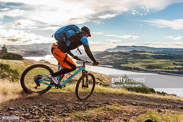 mountain bikers ride along columbia river. - hood river stock pictures, royalty-free photos & images