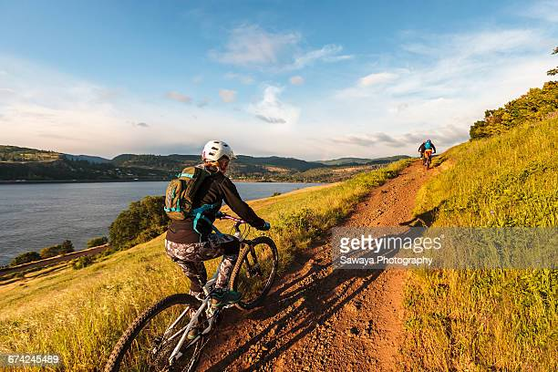 mountain bikers ride along columbia river. - hood river valley stock photos and pictures