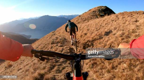 mountain bikers ride along mountain ridge in the morning - escaping stock pictures, royalty-free photos & images