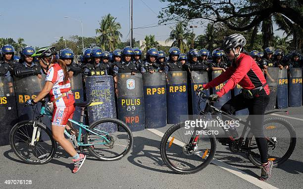 Mountain bikers ride past Philippine riot police in Manila on November 14 ahead of the Asia-Pacific Economic Cooperation summit. The Philippines...