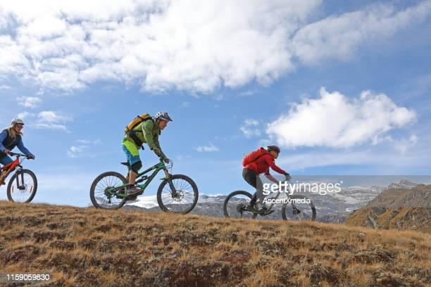 mountain bikers ride through alpine grasses below the matterhorn mountain - zermatt stock pictures, royalty-free photos & images