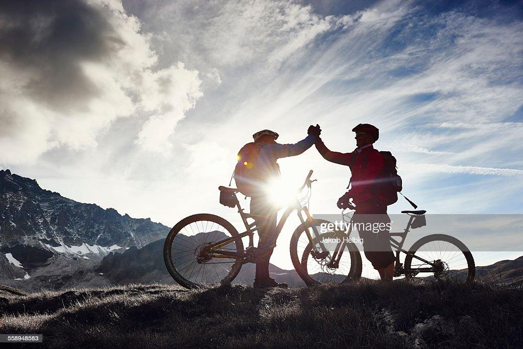 Mountain bikers shaking hands, Valais, Switzerland : Stock Photo
