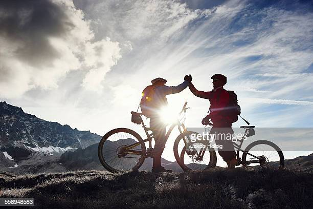 Mountain bikers shaking hands, Valais, Switzerland
