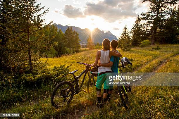 Mountain bikers watch sunset at trail edge, meadow