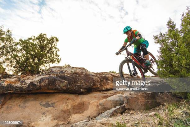 mountain biking adult female in western colorado desert arid climate late evening - colorado stock pictures, royalty-free photos & images