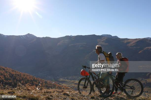 Mountain biking couple ascend slope, with mountainous valley below