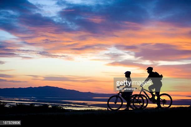 マウンテンバイクカップルサンセットの眺めをお楽しみいただけます。
