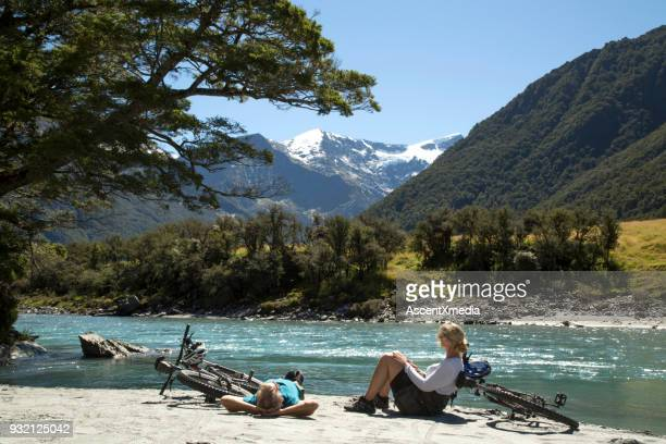 mountain biking couple relax on river bank - new zealand stock pictures, royalty-free photos & images