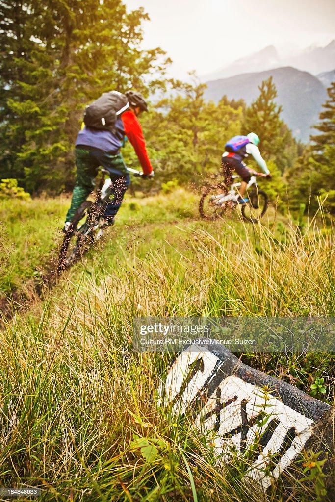 Mountain biking couple riding dirt trail : Stock Photo