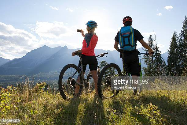 Mountain biking couple take smart phone pic,meadow
