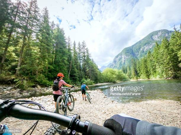 pov, mountain biking family exploring river and lake shore - vancouver canada stock pictures, royalty-free photos & images