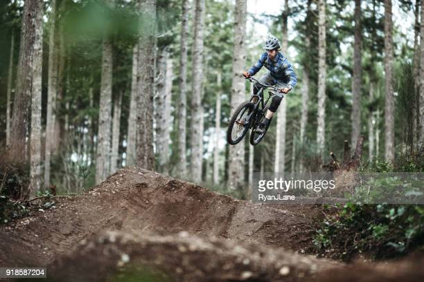 mountain biking man gets big air off jump - mountain bike stock pictures, royalty-free photos & images