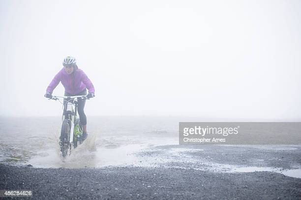 Mountain Biking - Woman Rider Splashing Through a Puddle