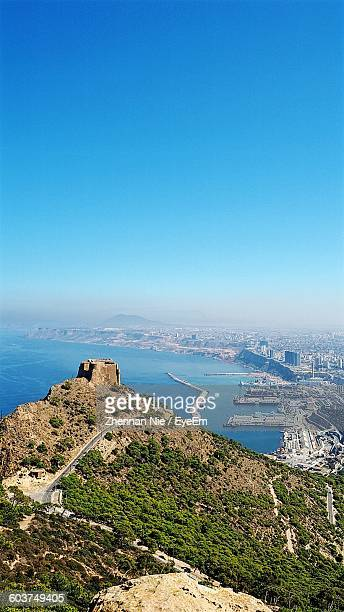 Mountain By City And Sea Against Clear Blue Sky