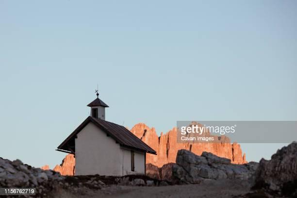 mountain chapel with high rocky ridge on background at twilight. tre cime di lavaredo national park, dolomites, italy - ベッルーノ ストックフォトと画像