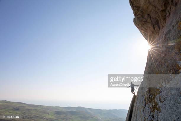 alpinista sale parete rocciosa all'alba - coraggio foto e immagini stock