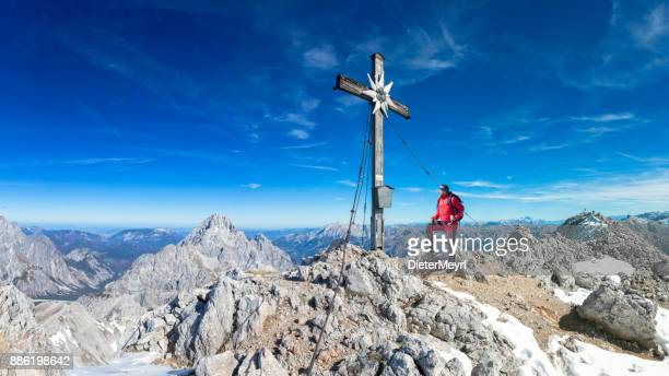 Mountain Climber at summit cross of Mount Großer Hundstod - Nationalpark Berchtegaden