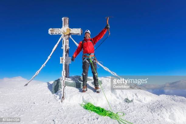 Mountain Climber at summit cross on top of Grossglockner, Austrian Alps