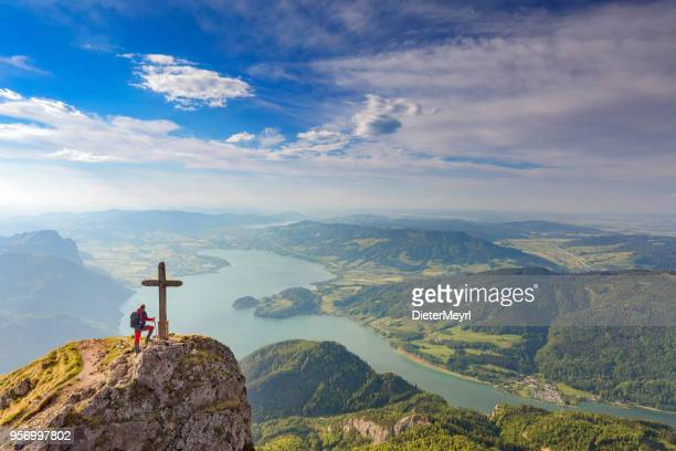 mountain climber at summit cross on top of mount schafberg, alps - salzburger land stock pictures, royalty-free photos & images
