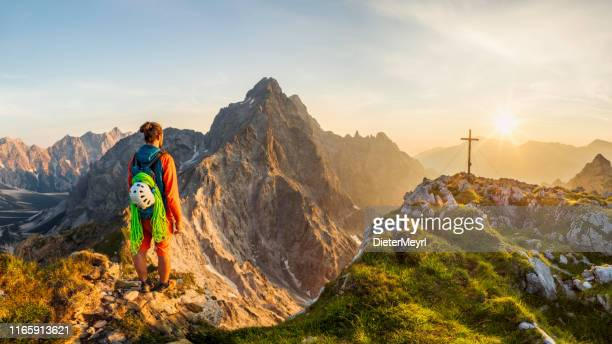 mountain climber at summit cross with glory view to watzmann east wall, berchtesgaden national park - berchtesgaden stock pictures, royalty-free photos & images