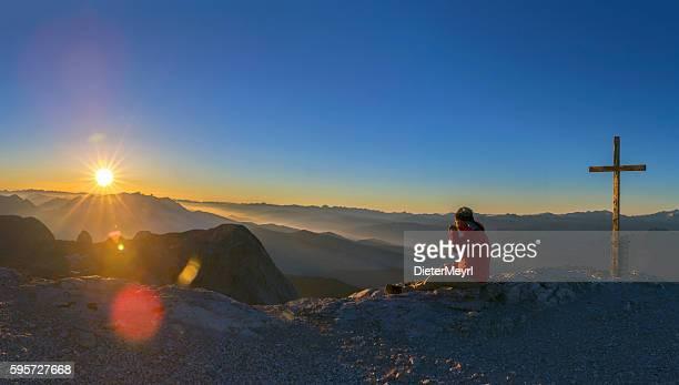 mountain climber enjoy the sunrise at mountain peak hochkönig - kreuz stock-fotos und bilder