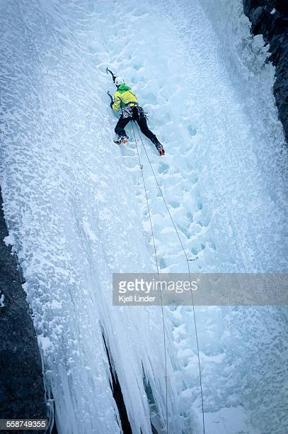 Mountain climber on ice-covered rock face