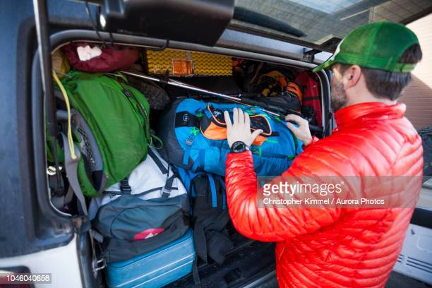 mountain climber putting backpack into car trunk - car trunk stock pictures, royalty-free photos & images