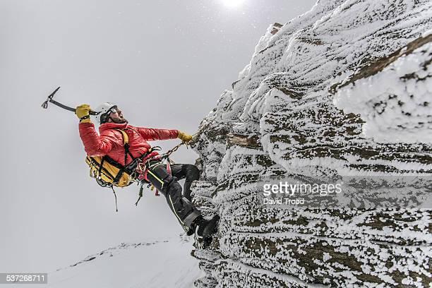 Mountain climber scaling icey ledge