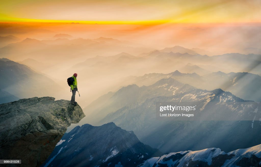 Mountain climber standing on edge of mountain, looking at view, Courmayeur, Aosta Valley, Italy, Europe : Stock Photo