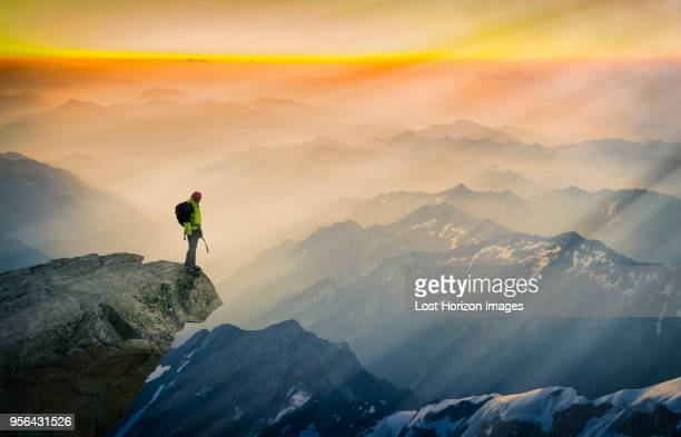 mountain climber standing on edge of mountain, looking at view, courmayeur, aosta valley, italy, europe - bergpiek stockfoto's en -beelden