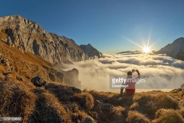 mountain climber take picture with mobile phone at sunrise - alps - panoramica foto e immagini stock