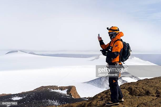 A mountain climber uses a cell phone to photograph Mount Erebus an active volcano from a mountaintop.