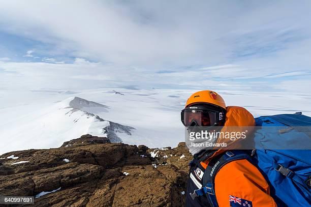 A mountain climber views Mount Erebus an active volcano from a mountaintop.