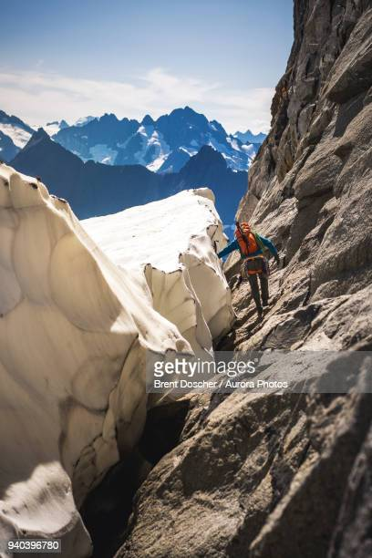 Mountain climber walking around glacier bergschrund at base of Mount Torment, North Cascades National Park, Washington State, USA