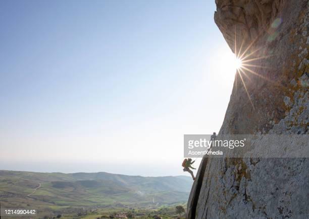 los escaladores de montaña ascienden la cara de roca al amanecer - montañismo fotografías e imágenes de stock